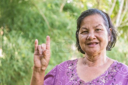 Old Thai woman smiling and willing to show I love you hand sign