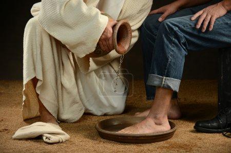 Photo pour Jésus lavant les pieds de l'homme moderne portant un jean - image libre de droit