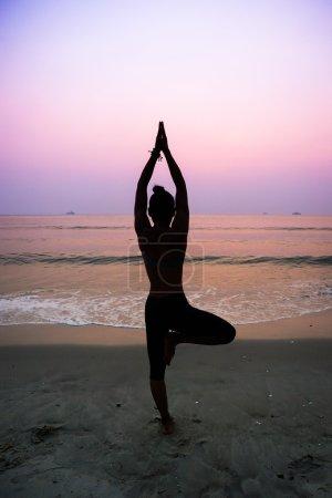 Photo pour Silhouette jeune femme pratiquant le yoga sur la plage au lever du soleil - image libre de droit
