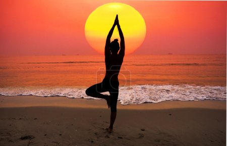 Photo for Silhouette young woman practicing yoga on the beach at sunrise - Royalty Free Image