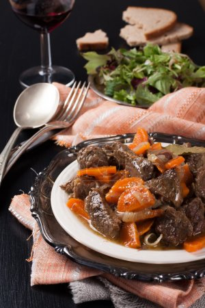Photo for Plate of beef stew with a green salad on dark background. Very Shallow depth of field. - Royalty Free Image