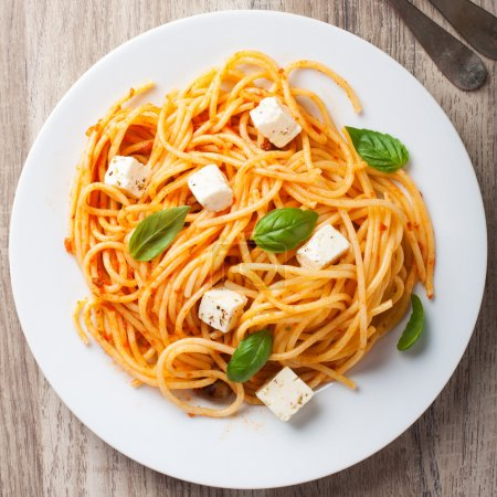 Photo for Spaghetti with tomato sauce, feta cheese and basil leaves on white plate on wooden background. Italian healthy food background. View from above. - Royalty Free Image