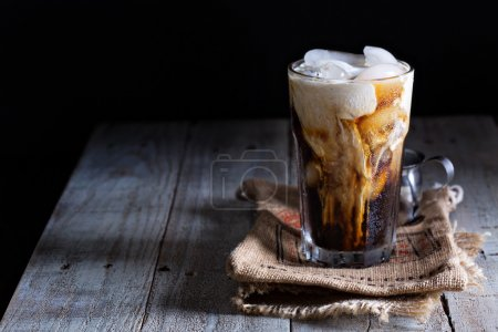 Photo for Iced coffee in a tall glass with cream poured over - Royalty Free Image