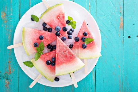 Photo for Fresh watermelon popsicles with blueberries cut on ice top view - Royalty Free Image