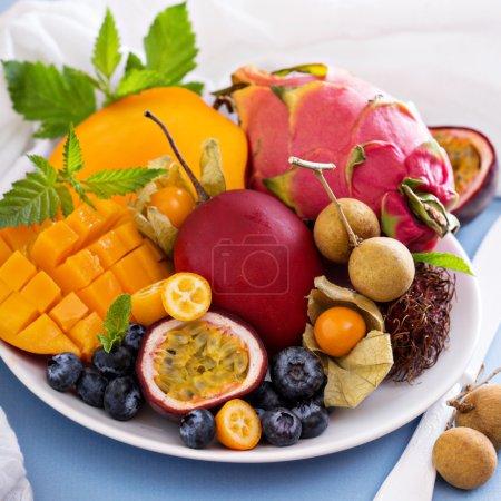 Photo pour Variété de fruits exotiques sur assiette blanche - image libre de droit