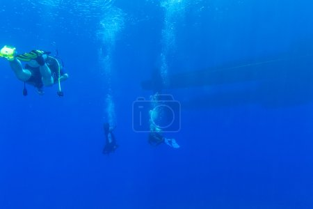 Group of Divers near Boat Underwater