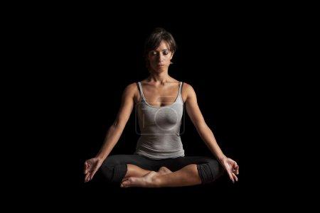 Photo pour Femme pratiquant la méditation de yoga sur fond noir - image libre de droit