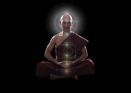 Buddhist monk in meditation pose on black backgrou...