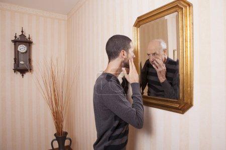 man looking at older himself