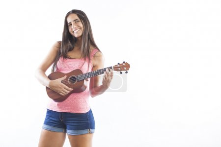 Young beautiful brunette woman playing ukulele