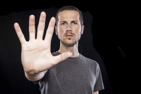 Foto de Retrato de joven guapo haciendo señal de stop gesto con la mano sobre fondo negro - Imagen libre de derechos
