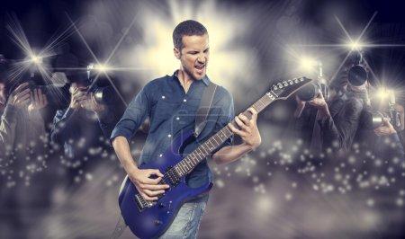 young man playing electric guitar