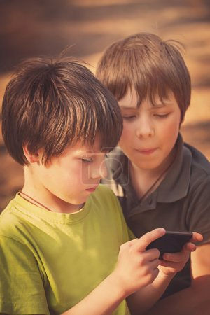 Child playing mobile phone outdoors