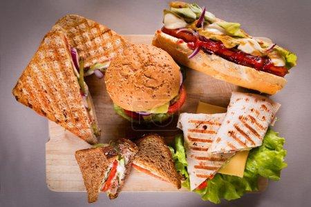 Photo pour Assiette de restauration rapide avec sandwichs hamburger hot dog et enveloppement de poulet - image libre de droit