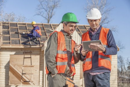 Photo for 3 person construction crew standing in front of newly built house - Royalty Free Image