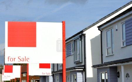 Photo pour Maisons neuves à vendre avec des signes d'agents immobiliers à l'extérieur. - image libre de droit