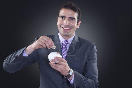 businessman putting coin in piggy bank