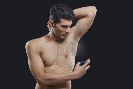 Man spraying deodorant on underarm