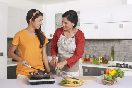 Mother teaching daughter to cook