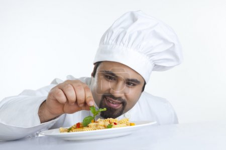 Chef decorating pasta with leaf