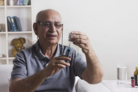 Man filling syringe with insulin