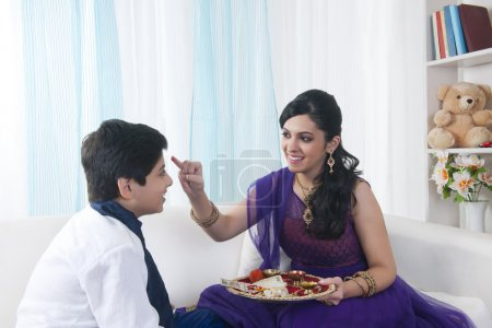 Sister applying tilak to her brother