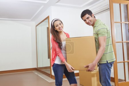 man and young woman carrying box