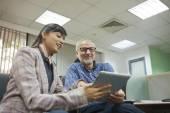 Executives looking at digital tablet