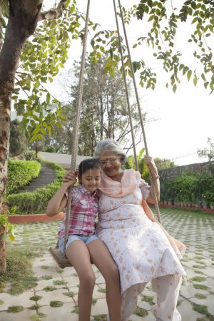 Grandmother and granddaughter sitting on a swing