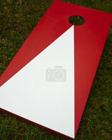 Photo for Plain red and white wooden cornhole toss game board on grass. - Royalty Free Image