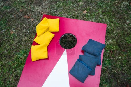 Photo for Blue and yellow bean bags stacked on cornhole toss game board. - Royalty Free Image