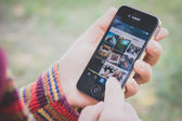Hand holding Iphone and using Instagram application