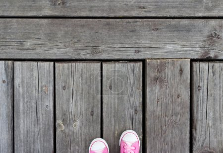Pink shoes on a old wooden footbridge