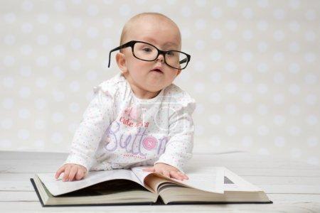 Photo pour Drôle de portrait d'une jolie petite fille dans des lunettes couché sur un grand livre - image libre de droit