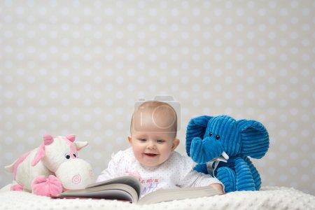 Photo pour Bébé fille souriante lisant un livre avec de petits amis jouets - image libre de droit