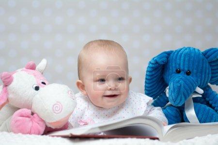 Photo pour Bébé fille heureuse lisant un livre avec de petits amis jouets - image libre de droit