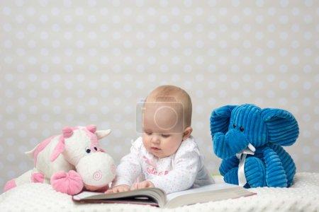 Photo pour Bébé fille lisant un livre avec de petits amis jouets - image libre de droit
