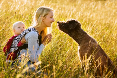 Young mother with her daughter and dog resting in ...