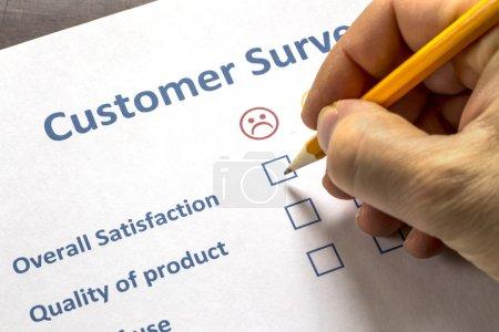 Photo pour Homme remplissant un sondage auprès des clients avec cases à cocher sélectionnant pour montrer son insatisfaction au service offert - image libre de droit