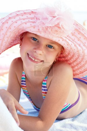 Happy cute child lying down on deckchair of beach resort