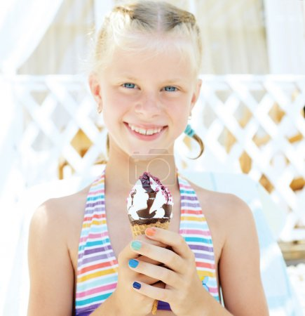 Little girl in the bright bathing suit eating a delicious ice cream on the beach