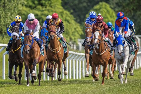 Group of colorful jockeys and horses in fast pace