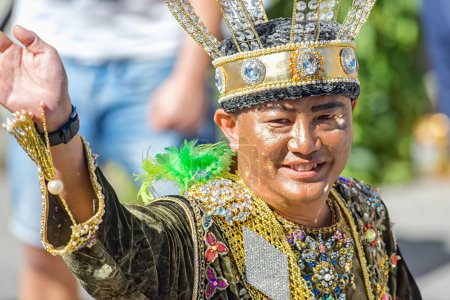Asian man in a crown and fancy clothes at the Pride parade