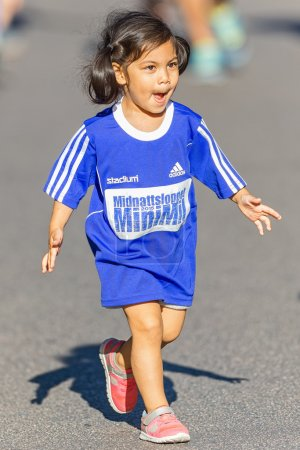 Young girl with big blue shirt running the Minimil for the young