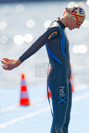 Female triathlete standing up and stretching at Womens ITU World