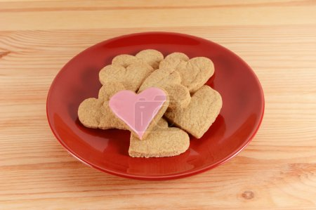 Photo for Frosted and plain heart-shaped biscuits piled on a red plate, on a wooden table - Royalty Free Image