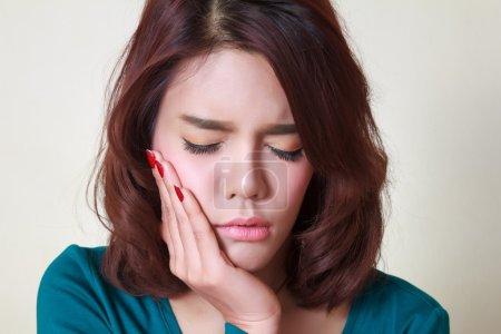 Photo pour Adolescente pressant sa joue meurtrie avec une expression douloureuse comme si elle avait un terrible mal de dent . - image libre de droit