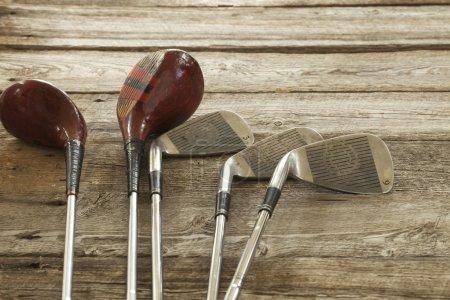 Photo pour Vieux clubs de golf sur la surface rugueuse en bois - image libre de droit