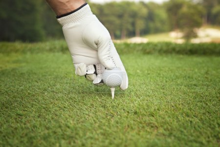 Selective focus of golfer's hand placing ball on tee