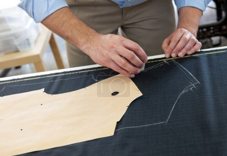 Tailor or clothing designer at work in his studio